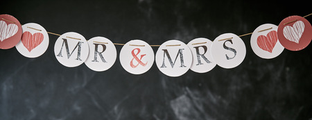 mrs: Mr and Mrs wedding garland panoramic banner with individual letters and hearts on circles over a grunge chalkboard background with copy space Foto de archivo