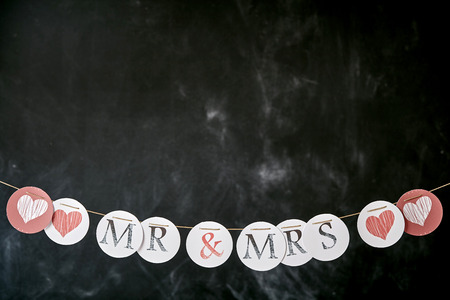 mrs: Newlyweds marriage border for Mr and Mrs with lettering and romantic hearts on circles on a string forming a bottom border and slate with copy space