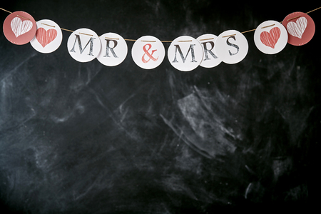 mrs: Wedding garland with Mr and Mrs and hearts on individual circles forming a top border over grungy slate with copy space