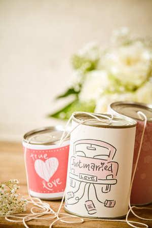 Leuk wit en roze zijn net getrouwd met metalen blikjes met een touwtje voor een concept over jonggehuwden die na de ceremonie weggaan
