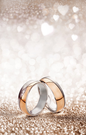 Romantic wedding ring celebration background with two gold rings balancing upright over a light sparkling background with white hearts and copy space for an invitation or greeting card