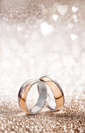 Romantische trouwring viering achtergrond met twee gouden ringen rechtop balanceren op een lichte sprankelende achtergrond met witte harten en kopieer de ruimte voor een uitnodiging of wenskaart Stockfoto