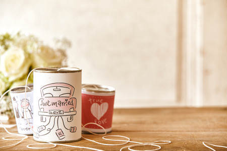 Set of decorated cans with strings with obscured bouquet and copy space for marriage or newlywed theme Stock Photo