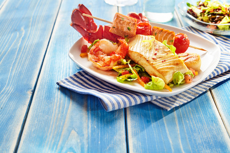 Fresh seafood snack salad on square plate over blue wooden table with copy space