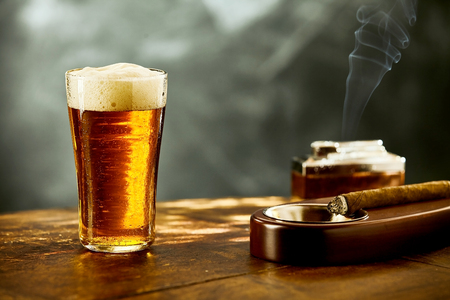 Single frothy pint of beer with a burning cigar in an ashtray on an old wooden table or counter in a nightclub or bar with copy space