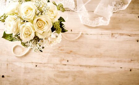 High Angle Still Life of Bridal Bouquet with Delicate White Roses and Greenery on Rustic Wooden Table with Feminine Lace Veil and Copy Space