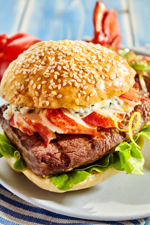 Detailed close up on bacon, lettuce and mayonnaise sesame seed bund surf and turf hamburger on plate