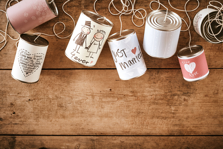 Wedding greetings on various stringed cans over brown wooden background with copy space