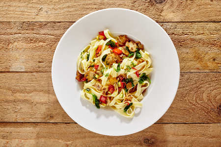 energising: Italian fettuccine or tagliatelli pasta with mushrooms, tomato and fresh basil for an energising carbohydrate meal viewed from overhead on wood