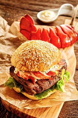 Thick hamburger with bacon on cutting board with freshly cooked lobster tail and mayonnaise behind it