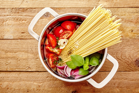steel making: Diced fresh ingredients for making Italian spaghetti standing ready in a stainless steel pot with a bundle of dried noodles, overhead view