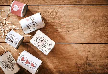 top down car: High Angle Still Life of Tin Cans Tied with String and Decorated with Congratulatory Wedding Messages on Rustic Wooden Table with Copy Space - Traditional Newlywed Marriage Decorations