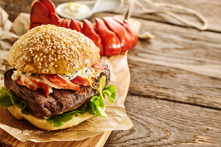 red cooked: Freshly cooked bacon, lettuce and mayonnaise hamburger with red lobster tail on cutting board