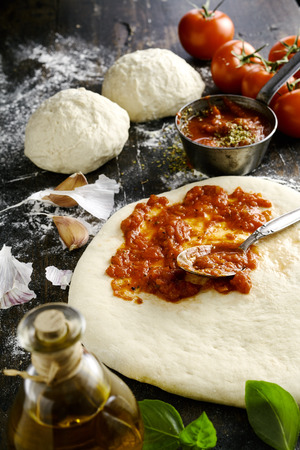 pizza base: Preparing a traditional Italian pizza with a closeup view of thick fresh tomato paste being spread on an uncooked pastry base surrounded by flour, basil, olive oil, garlic and mounds of dough