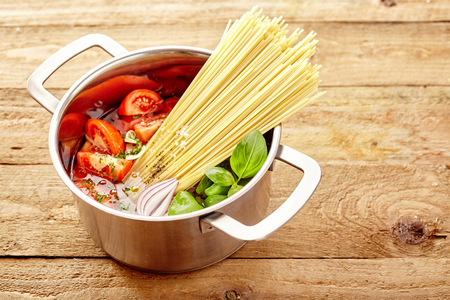 semolina pasta: Ingredients for Italian spaghetti standing ready for cooking one pot with dried noodles, tomato, onion and fresh basil, high angle on a natural wood plank background
