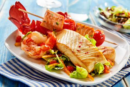 Arrangement of seafood appetizers on rectangular plate. Includes shrimp, lobster and fish meat on skewer with vegetables.