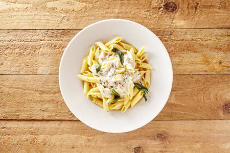 centered: Delicious creamy Italian penne pasta starter with pepper seasoning and fresh basil viewed from above on rustic wooden centered with copy space