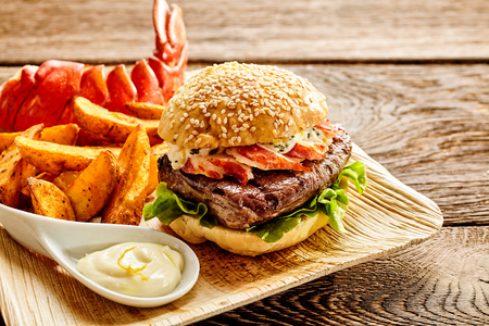 Sesame bun hamburger filled with bacon, lettuce and beef with large baked potato fries and lobster tail, mayonnaise on the side