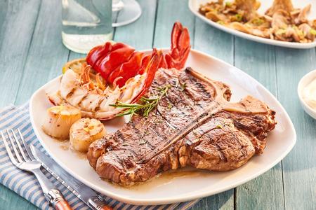 잘된 스타일 T 뼈 스테이크와 랍스터 플레이트 구이 야채 옆에 테이블에 접시와 물 유리