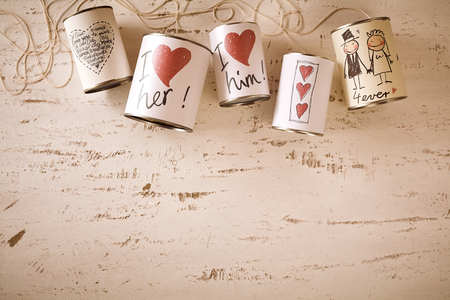 drawn metal: Hand drawn love and marriage symbols on metal cans attached with string over scratched up white background with copy space