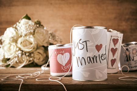 Barattoli di latta per un auto matrimonio con schizzi disegnati a mano raffiguranti cuori rossi e testo - Just Married - su un tavolo in legno con bouquet da sposa di rose bianche Archivio Fotografico - 62635643
