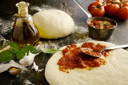 Ingrediënten voor een heerlijke zelfgemaakte Italiaanse pizza met een lage hoek weergave van verse tomatenpasta die op een ongekookte deegbasis wordt verspreid met knoflook, basilicumbladeren en olijfolie langs Stockfoto