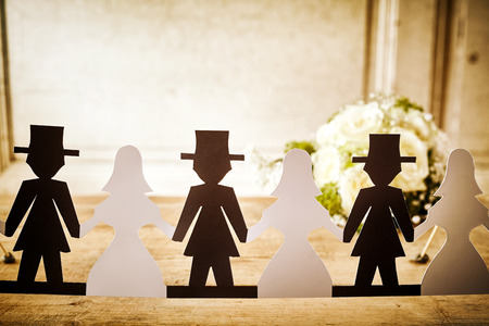 wooden doll: Bride and Groom Paper Doll Cut Outs Lined Up on Rustic Wooden Table in front of White Rose Bridal Bouquet - Decorations at Wedding or Bridal Shower in Newlywed Concept Image Stock Photo