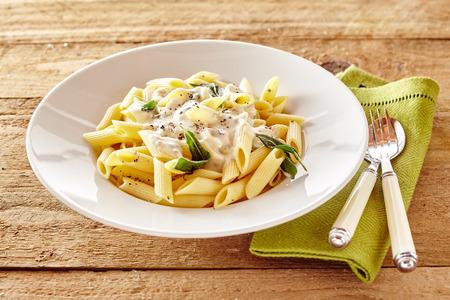 Plaat van Italiaanse penne pasta gegarneerd met een romige saus met basilicum en kruiden geserveerd op een rustieke houten tafel met keukengerei en servet
