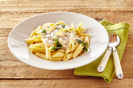 Plate of Italian penne pasta topped with a creamy sauce with basil and seasoning served on a rustic wooden table with utensils and napkin Фото со стока
