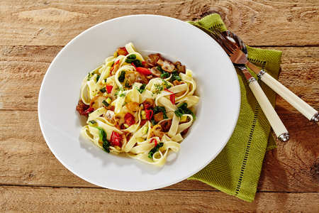 linguine pasta: Energy rich Italian linguine pasta with mushrooms, basil and tomato garnished with fresh herbs for carbo-loading for sport, high angle view with utensils and napkin