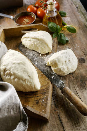 vintage kitchen: Huge mound of pizza dough being portioned out into three portions for individual bases in a rustic kitchen with vintage utensils and fresh ingredients behind Stock Photo