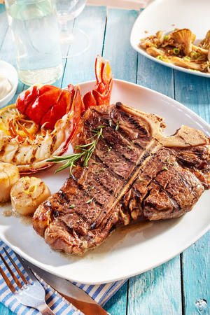 Delicious well done surf and turf steak and lobster meal with seafood side items on blue wooden table in front of plate of roasted vegetables