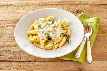 pasta sauce: Plate of Italian Penne pasta topped with a formaggio creamy savory sauce and basil served in a white dish on a rustic wood table Stock Photo
