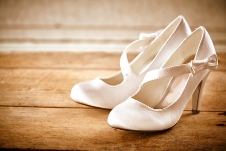 wood floor: Close Up Still Life of Pair of White Satin Bridal Shoes with High Heels and Angled Strap with Small Bows Resting on Rustic Wooden Floor or Table with Copy Space