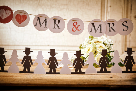 outs: Bride and Groom Paper Doll Cut Outs Lined Up on Rustic Wooden Table in front of White Rose Bouquet and Underneath Mr and Mrs Banner Hanging Up at Wedding Celebration or Bridal Shower Stock Photo