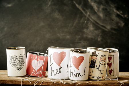 free backgrounds: Love and marriage handicrafts as strung together metal cans for concept about newlyweds. Includes dark chalkboard background with copy space.
