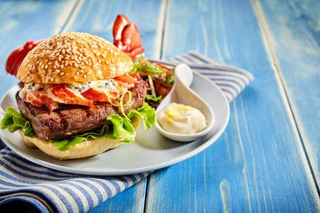 Bacon, sla en mayonaishamburger op plaat met exemplaarruimte over blauwe houten achtergrond