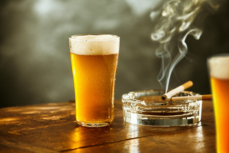 Ice cold lager or beer with a burning cigarette resting on a glass ashtray on a rustic wooden counter in a tavern, nightclub or pub, low angle close up