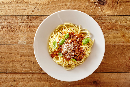 Plaat van heerlijke Spaghetti Bolognaise of Bolognese Met Hartig Gehakt Biefstuk En Tomatensaus Gegarneerd Met Parmezaanse Kaas En Basiliek, Overhead View