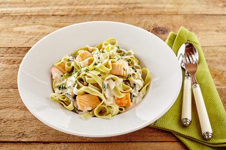 Seafood tagliatelli or fettuccine Italian pasta with salmon fillet topped with a creamy sauce and fresh herbs