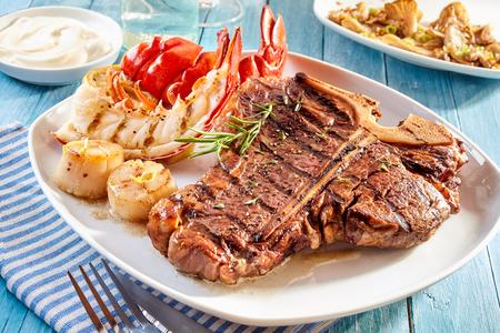 Bereid surf en gras goed gedaan steak en kreeft maaltijd met bijgerechten van crab cakes, garnalen en mayonaise duik op blauwe houten tafel