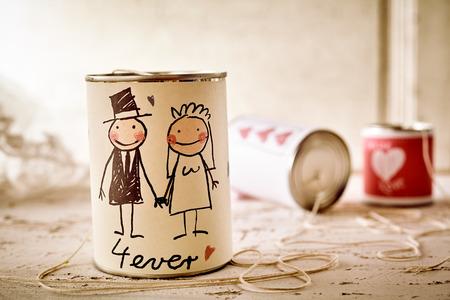 Garabateado masculina y femenino par de recién casados ??en lata con la cadena en la tabla para el concepto sobre el matrimonio