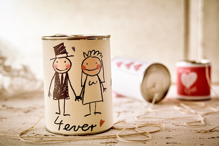 Scribbled newlywed male and female couple on can with string on table for concept about marriage