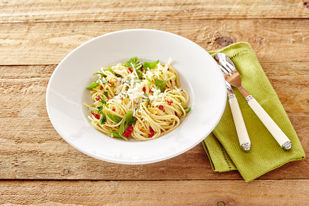 olio: Plate of Italian spaghetti aglio olio parmigiana with basil and tomato garnished with grated parmesan cheese viewed high angle with napkin and tableware on rustic wood Stock Photo