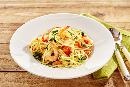 Gourmet Italian seafood pasta with shrimp or prawn tails, tomato and basil served in a white dish on a rustic wood table Stock Photo