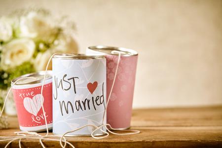 mariage: Close Up Nature morte de boîtes en fer blanc décoré avec des messages de félicitation et ficelés pour glisser derrière une voiture suiveuse de mariage, Se reposer sur table en bois rustique avec Espace texte