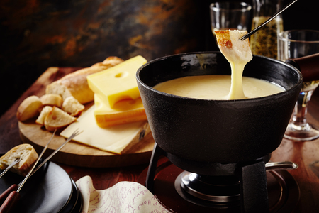 Dipping into a tasty traditional Swiss cheese fondue with bread on a fork, assorted cheese ingredients and white wine behind, close up view Imagens - 62635575