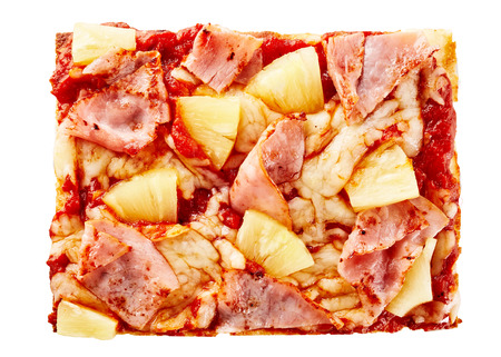 Italian pizza slice topped with tasty ham and pineapple wedges on a bed of melted mozzarella and tomato viewed close up from above on white Stock Photo