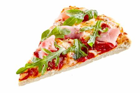 Thin base pizza slice topped with fresh arugula or rocket and thinly sliced parma ham with melted mozzarella and tomato Stock Photo