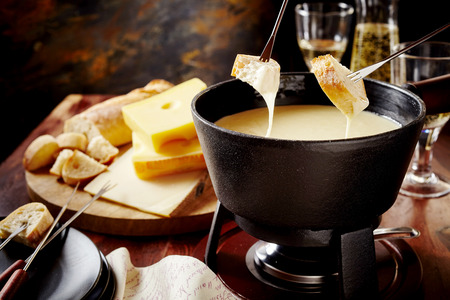 food concept: Dipping into a delicious cheese fondue made with a blend of assorted melted cheeses and wine or cider Stock Photo